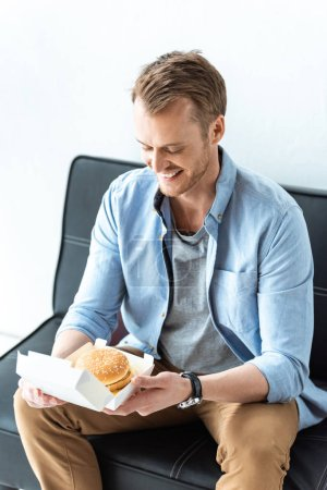 happy young businessman having lunch with burger while sitting on sofa in office