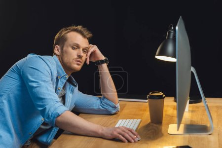 overworked young businessman sitting at table with computer and disposable coffee cup during late night in modern office