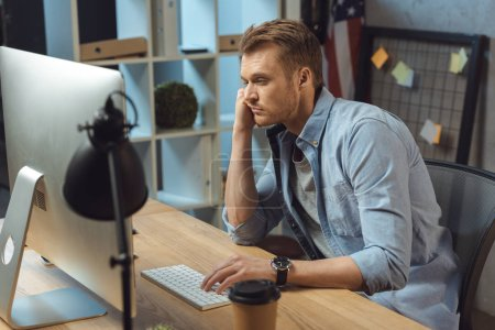 Photo for Selective focus of overworked businessman sitting at table with computer and disposable coffee cup during late night in modern office - Royalty Free Image