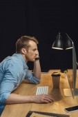 handsome overworked businessman sitting at table with computer and disposable coffee cup under desk lump during late night in modern office