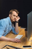 high angle view of tired businessman looking at camera while sitting at table with smartphone and computer during late night in office