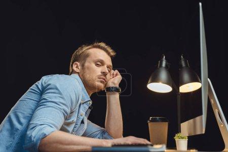 Foto de Vista de ángulo bajo de empresario joven con exceso de trabajo sentados en mesa con computadora y una taza de café desechables bajo escritorio terrón durante la noche en la oficina moderna - Imagen libre de derechos