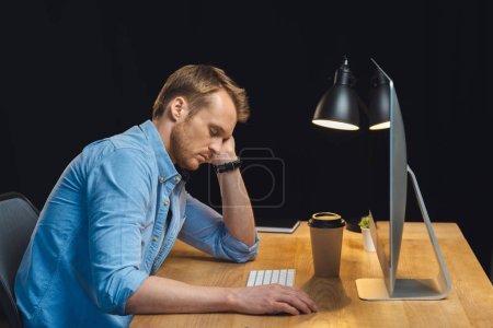 side view of businessman sleeping at table with computer and paper coffee cup during night time in office