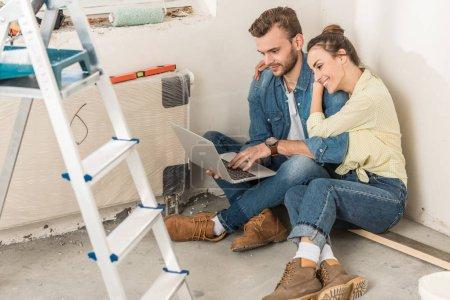 vue de la forte inclinaison du jeune couple à l'aide d'ordinateur portable tout en étant assis sur le sol dans Maison Neuve