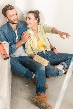 high angle view of happy young couple sitting on floor and pointing away during home improvement