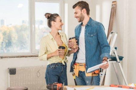 Foto de Feliz pareja joven con café para llevar y tableta digital durante la renovación - Imagen libre de derechos