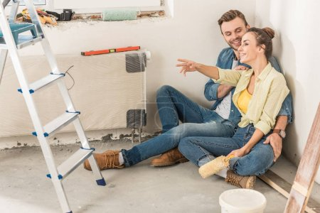 happy young couple sitting on floor and looking away during home improvement