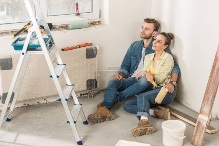 high angle view of pensive young couple sitting together on floor and looking away at new home