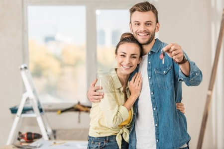 Photo for Happy young couple holding key from new apartment and smiling at camera - Royalty Free Image