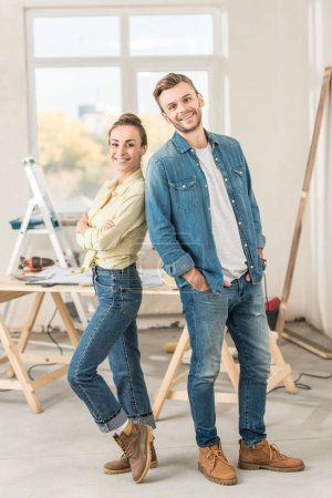 happy young couple standing back to back and smiling at camera during house repair