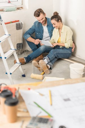 Photo for High angle view of smiling young couple using digital tablet while sitting on floor during house repair - Royalty Free Image