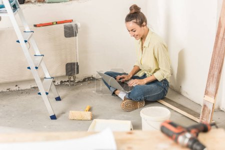 Photo for High angle view of smiling young woman using laptop while sitting on floor at new house - Royalty Free Image
