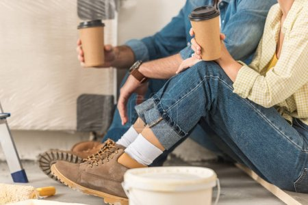 cropped shot of young couple holding coffee to go and sitting on floor during home improvement