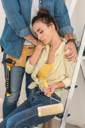 cropped shot of man with toolbelt hugging tired girlfriend sitting on step ladder in new house
