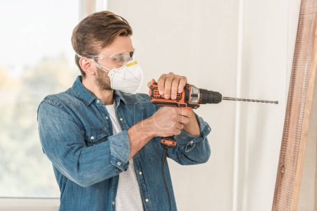 young man in protective mask and goggles using electric drill during house repair
