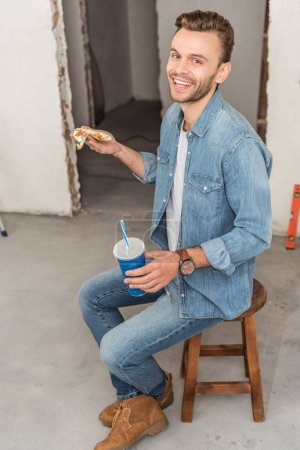 high angle view of happy young man holding paper cup with refreshing beverage and smiling at camera in new home
