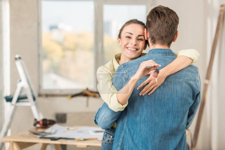 happy young woman hugging boyfriend and holding key from new apartment