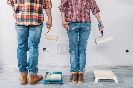 Photo for Low section of couple holding paint rollers and painting wall in new house - Royalty Free Image