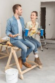 happy young couple holding pizza and paper cups during house repair