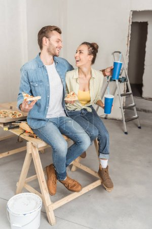 Photo for Happy young couple with pizza and paper cups sitting together and smiling each other during repairment - Royalty Free Image