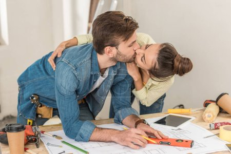 young couple kissing while man marking blueprint with level tool
