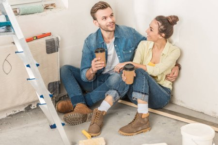 high angle view of smiling young couple holding paper cups and sitting on floor in new apartment