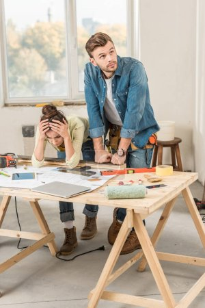 upset young couple leaning at table with tools during repairment