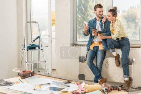 Photo pour Heureux jeune couple tenant les gobelets en papier et à l'aide de la réparation de smartphone - image libre de droit