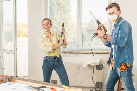 happy young couple holding tools and having fun in new apartment