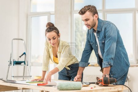 Photo for Young couple looking at blueprint during house repair - Royalty Free Image
