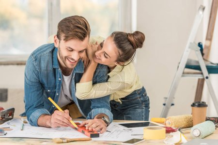 happy young woman hugging smiling boyfriend marking blueprint with level tool during house repair