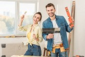happy young couple holding tools and smiling at camera during house repair