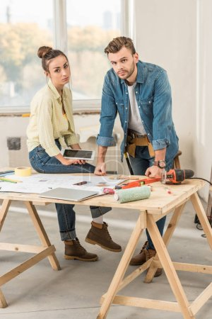 Photo for Upset young couple leaning at table with tools and looking at camera during renovation - Royalty Free Image