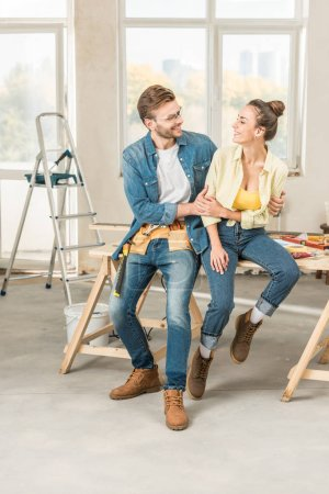 Photo for Happy young couple hugging and smiling each other while sitting on table with tools - Royalty Free Image