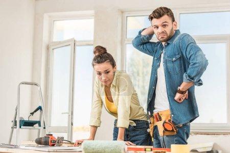 Foto de Situación incierta pareja joven junto a la mesa con las herramientas durante la reparación - Imagen libre de derechos