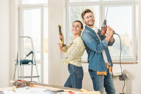 Photo for Happy young couple holding tools and smiling at camera during house repair - Royalty Free Image