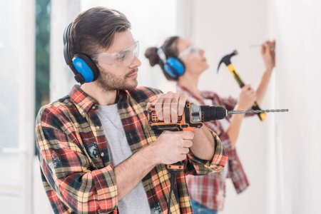 young couple drilling and hammering wall during repairment