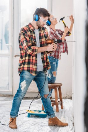 Photo for Side view of young couple drilling and hammering wall during renovation - Royalty Free Image