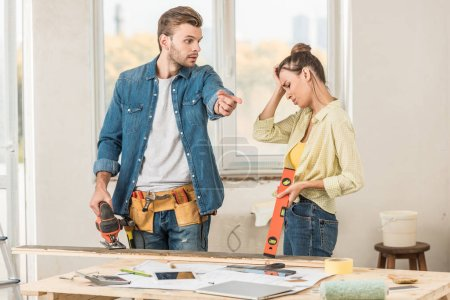 emotional young couple holding tools and quarreling during renovation