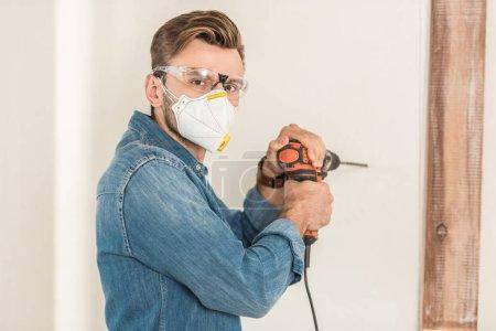 Photo pour Jeune homme en vêtements de travail protecteurs à l'aide d'une perceuse électrique et regardant la caméra lors de la réparation de la maison - image libre de droit