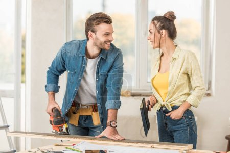 Foto de Feliz pareja joven sosteniendo herramientas y sonriendo uno al otro durante la reparación - Imagen libre de derechos