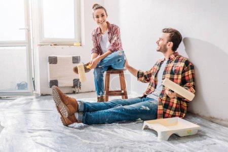 Foto de Feliz pareja joven con pintura rodillos y descansando durante la reparación - Imagen libre de derechos