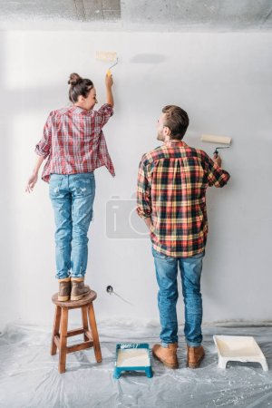 back view of happy young couple painting wall with paint rollers