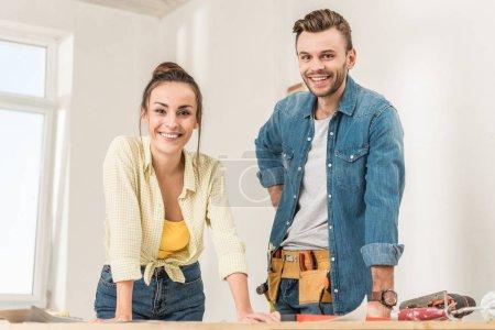 Foto de Que se inclina en la pareja joven feliz en mesa con herramientas y sonriendo a la cámara durante la reparación de la casa - Imagen libre de derechos