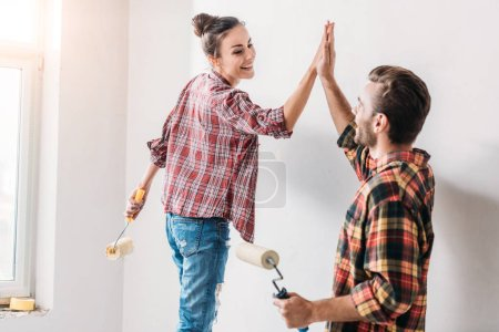 happy young couple giving high five while painting wall in new apartment
