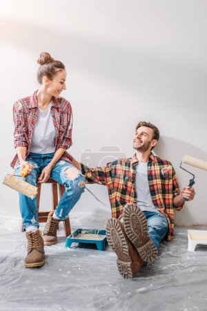 Photo pour Jeune couple en damiers chemises tenant peindre les rouleaux et souriant mutuellement - image libre de droit