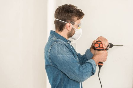 young man in protective workwear using electric drill at wall during house repair