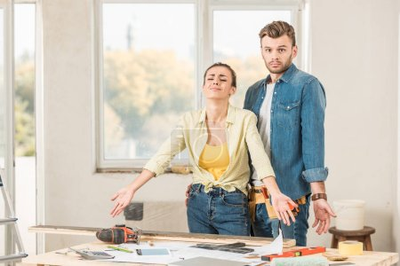 Photo for Upset young couple standing near table with tools during home repairment - Royalty Free Image