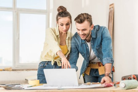 young couple using laptop during home improvement