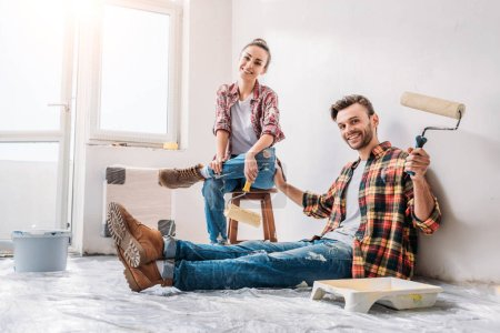 happy young couple holding paint rollers and smiling at camera during renovation